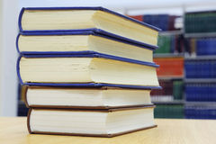 Stacking books on library table. Against bookshelf Royalty Free Stock Photos