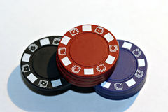 Stacking chips. Red, blue, and black poker chips on a white background stock photos