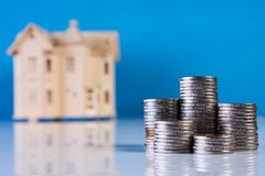 A stacking coins and house model. On blue background with copy space. Saving money for real estate with buying a new home and loan for prepare in the future Stock Photography