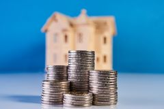 A stacking coins and house model. On blue background with copy space. Saving money for real estate with buying a new home and loan for prepare in the future Royalty Free Stock Photos