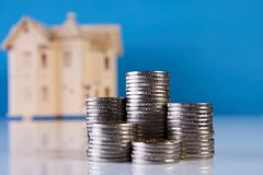 A stacking coins and house model. On blue background with copy space. Saving money for real estate with buying a new home and loan for prepare in the future Stock Photo