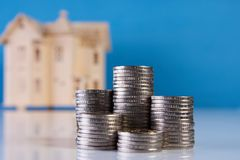 A stacking coins and house model. On blue background with copy space. Saving money for real estate with buying a new home and loan for prepare in the future Stock Photos