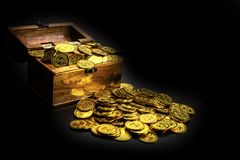 Gold Coin in treasure chest on black background stock photography