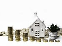 Stacking gold coins tower and house, saving money and loan for construction real estate and home concept. Stacking gold coins tower and house, flower cactus royalty free stock images
