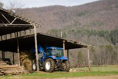Stacking Hay/Tractor/Barn. A worker on a farm stacking hay at the barn royalty free stock photo