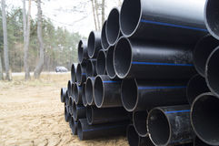 Stacking a large diameter water pipes of polyethylene. In an open area for the construction of water systems stockpiled water pipes of large diameter stock image