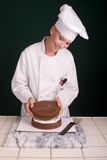 Stacking Layers. Passive posed smiling female Pastry Chef stacking a layer of chocolate devil's food cake atop a layer of white buttercream filling Stock Photography