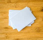 Stacking of a mockup empty white business card on a wooden background , template for business branding design. Stacking of a mockup empty white business card on royalty free stock image