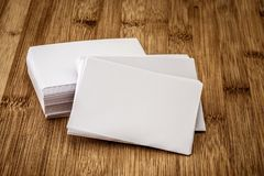 Stacking of a mockup empty white business card on a wooden background , template for business branding design. Stacking of a mockup empty white business card on stock photo
