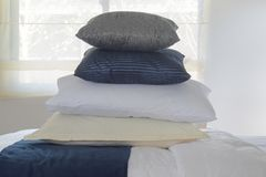Stacking pillows on bed with wall and window in background royalty free stock photo