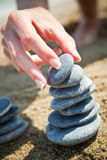 Stacking stones. Woman hand stacking stones on the beach Royalty Free Stock Image