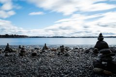 Stacking stones on pebble beach. Stacked stones on a beach at lake Pyhäjärvi on an early spring day in Tampere, Finland. Long esposure Royalty Free Stock Photography