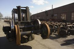 Stacking train-wheels. Man stacking train-wheels outside factory Royalty Free Stock Photo