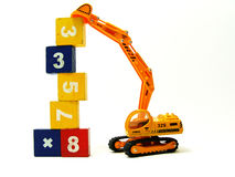 Miniature shovel-loader stacking up cubes Royalty Free Stock Photo