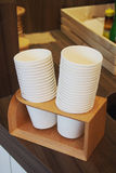 Stacking white paper cups. On timber holder in coffee shop Royalty Free Stock Photos