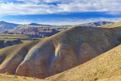 Stackmoln och röda berg i Khizi _ Arkivfoto