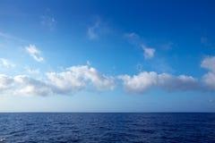 Stackmolnmoln i blå himmel över vattenhorisont royaltyfri fotografi