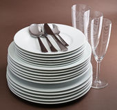 Stackof plate,cutlery and glasses. On brown background Royalty Free Stock Image