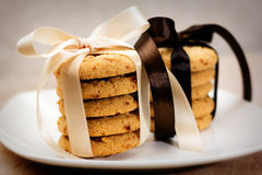 Stacks of apple chip cookies taped with silk ribbons. Close up of stacked apple chip cookies taped with silk ribbons on white china plate Royalty Free Stock Images