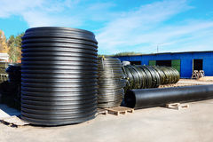 Stacks of black pvc plastic pipe outdoors with selective focus Stock Photo
