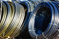 Stacks of black pvc plastic pipe outdoors with selective focus. Stacks of rolls black pvc plastic pipe outdoors with selective focus outside the warehouse royalty free stock images