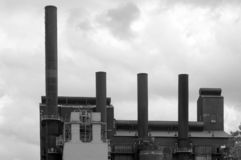Stacks in Black and White. Smoke Stacks on a steel mill photographed in black and white.  4 stacks lined up with a grey cloudy sky in the background.  Black and Royalty Free Stock Photos