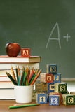 Stacks of books with blocks in front of chalkboard Royalty Free Stock Image
