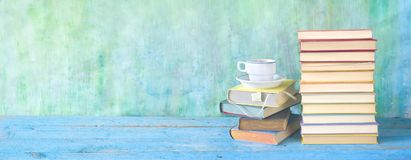 Stacks of books and a cup of coffee, panorama. Good copy space. Education, reading, literature, concept royalty free stock photo