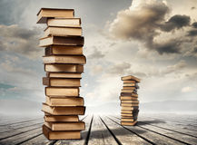 Stacks of books on tables. Stacks of books on wooden planks with the cloudy sky image in the background Royalty Free Stock Photography