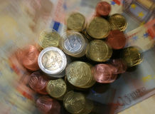 Stacks of burred Euro coins. Bizarre stacks of blurred Euro coins in front of 50 Euro banknotes stock photo