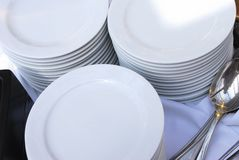 Stacks of Catering Plates with Spoons. Three stacks of white catering plates with silver spoons on a white table cloth Stock Photo