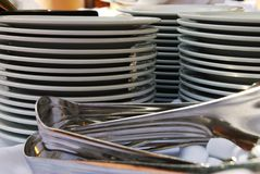 Stacks of Catering Plates with Tongs. Three stacks of white catering plates with silver tongs on a white table cloth Royalty Free Stock Photography