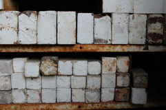 Stacks of ceramic kiln bricks on rusted metal shelves. Weathered old ceramic pottery kiln fire bricks, some with a crazed white salt glaze finish, stacked on Royalty Free Stock Photos