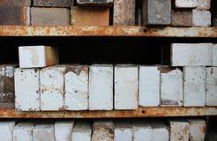 Stacks of ceramic kiln bricks on rusted metal shelves. Weathered old ceramic pottery kiln fire bricks, some with a crazed white salt glaze finish, stacked on Royalty Free Stock Photo
