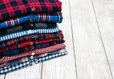 Stacks of checkered shirts. Stacks of checkered colorful shirts on a table Stock Photo