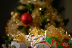 Stacks of Christmas Presents Under a Christmas Tree with Defocused Lights.  royalty free stock photography