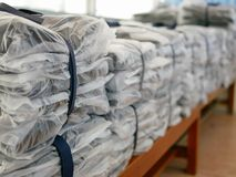 Stacks of clothes packed in plastic bags ready to be shipped / distributed. Selective focus and close up of stacks of clothes packed in plastic bags ready to be stock image