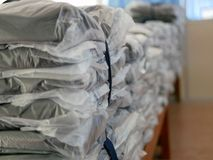 Stacks of clothes packed in plastic bags ready to be shipped / distributed. Selective focus and close up of stacks of clothes packed in plastic bags ready to be royalty free stock photo