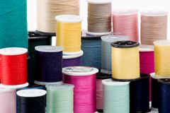 Stacks of clothing thread spools. Stack of multiple spools of clothing threads. Isolated on white stock images