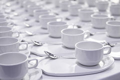 Stacks of coffee cups with silver teaspoons Stock Photos