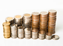 Stacks of coins on. Top view of stacks of coins increasing in height, on white  background Royalty Free Stock Photography