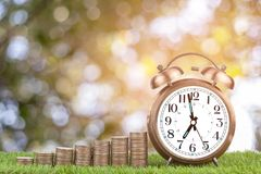 Stacks of coins and alarm clock on grass a background royalty free stock photos
