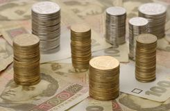 Stacks of coins on background of banknotes Stock Photo