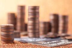 Stacks of coins. And bank cards on golden sparkle background. Financial concept Royalty Free Stock Images