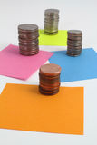 Stacks of coins on blank color notes Stock Image