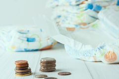 Stacks of coins with dipers at the background Royalty Free Stock Photography