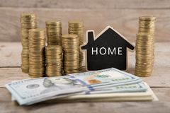 Stacks of coins and dollar bills, blackboard in the shape of a house with text & x22;HOME& x22; royalty free stock images