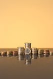 Stacks of coins on with a golden glow Stock Photography