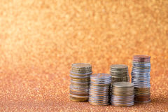 Stacks of coins. On golden sparkle background. Financial concept Stock Images