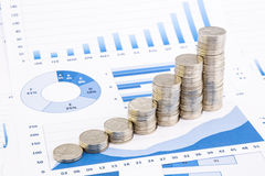 Stacks of coins on  graphs and charts Stock Photo